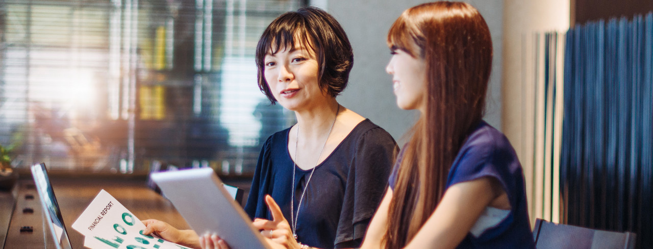 Two women look at financial reports